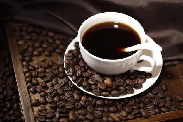 Palone ziarna kawy i filiżanka kawy na drewnianym stole