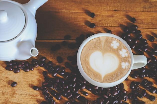 Palone ziarna kawy i gorąca kawa późno na stole.