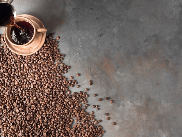 Palone ziarna kawy leżące na szarej ścianie przy filiżance kawy. widok z góry, miejsce na tex, miejsce na kopię.