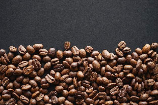 Palone ziarna kawy na czarnym papierze