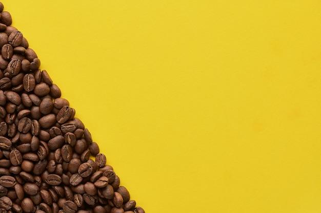 Palone ziarna kawy na żółtym tle z miejsca na kopię. zamknij widok z góry. zdjęcie wysokiej jakości