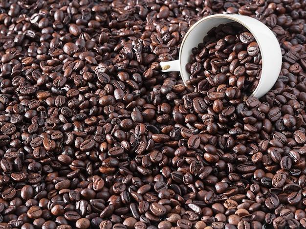 Palone ziarna kawy. świeża aromatyczna ciemna kawa. biała filiżanka do espresso leży w ziarnach. zbliżenie