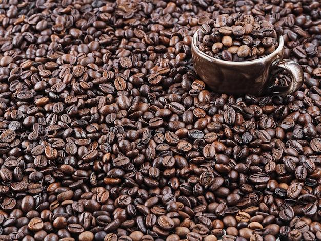 Palone ziarna kawy. świeża aromatyczna ciemna kawa. brązowy kubek do espresso stoi w ziarnach kawy. zbliżenie.