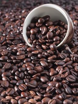 Palone ziarna kawy. świeże aromatyczne ciemne ziarna kawy i filiżanka espresso.