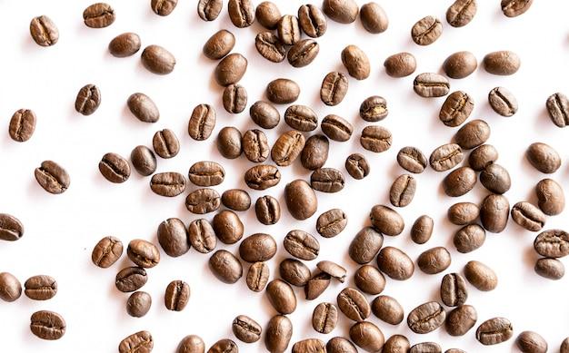 Palone ziarna kawy układają na białym tle