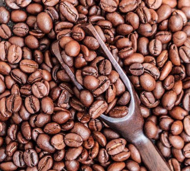 Palone ziarna kawy w drewnianą łyżką na czarno
