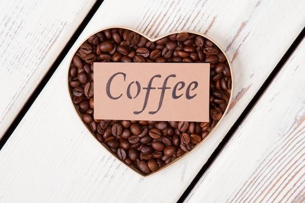 Palone ziarna kawy w formie serca. beżowy papier z kawowym słowem. białe drewno na powierzchni.