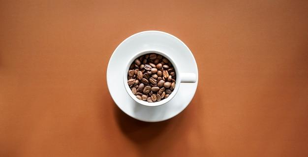 Palonych ziaren kawy w filiżance białej kawy z brązowym tłem