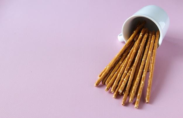 Paluszki chleba przewrócone na białą filiżankę na różowym tle z miejscem na kopię orientacja pozioma