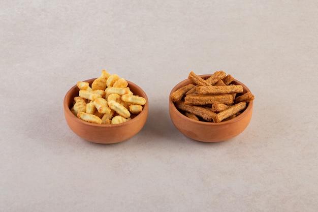 Paluszki chlebowe w miseczkach ustawione na beżowym stole.