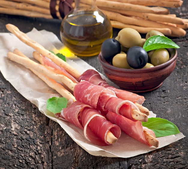 Paluszki grissini z szynką, oliwkami, bazylią na starym drewnianym