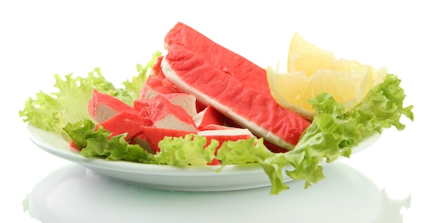 Paluszki krabowe z liśćmi sałaty i cytryną na talerzu na białym tle