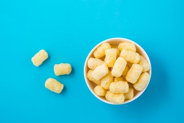 Paluszki kukurydziane w cukrze puder w misce na niebieskim stole. widok z góry