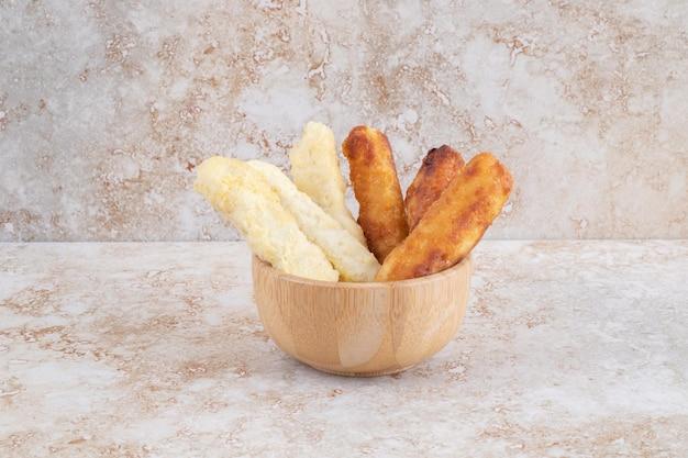 Paluszki serowe i grillowane kiełbaski w drewnianym kubku.