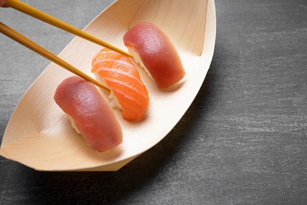 Paluszki trzymające surową rybę z ryżem