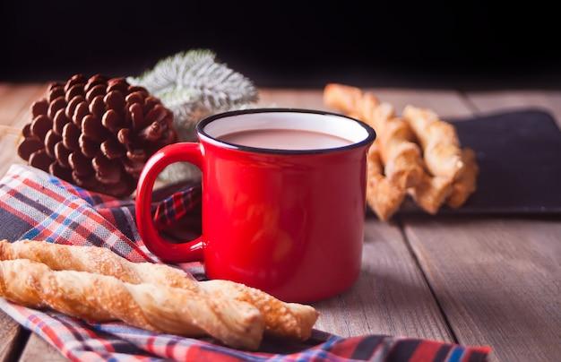 Paluszki z czerwonym kubkiem gorącej herbaty lub kawy na drewnianym stole
