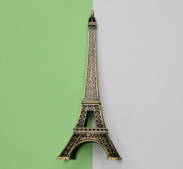 Pamiątkowa statuetka wieży eiffla na białym zielonym pastelu.