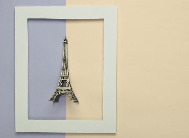 Pamiątkowa statuetka wieży eiffla w białej ramce na kolorowym pastelu.