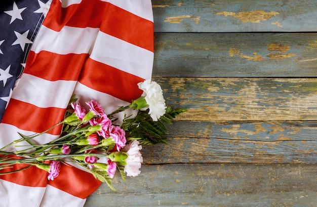 Pamięci różowe kwiaty goździków na amerykańskiej flagi na dzień pamięci