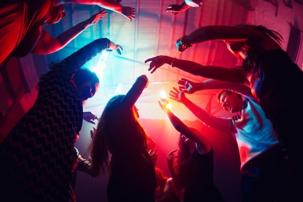 Pamiętać. tłum ludzi w sylwetce podnosi ręce na parkiecie na neonowym tle. życie nocne, klub, muzyka, taniec, ruch, młodzież. fioletowo-różowe kolory i poruszające dziewczyny i chłopcy.