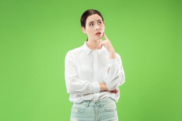 Pamiętaj wszystko. niech pomyślę. pojęcie wątpliwości. wątpliwa, zamyślona kobieta coś sobie przypomniała. młoda kobieta emocjonalna. ludzkie emocje, koncepcja wyrazu twarzy. studio. pojedynczo na modnej zieleni