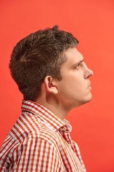Pamiętaj wszystko. niech pomyślę. pojęcie wątpliwości. wątpliwy, zamyślony mężczyzna coś sobie przypomina. młody człowiek emocjonalny. studio. pojedynczo na modnej czerwieni. profil