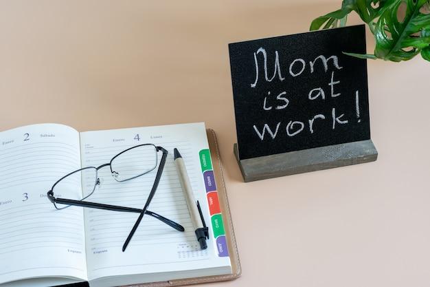 """Pamiętnik czasu otwartego, okulary i czarny wykrój z napisem """"mama jest w pracy"""". domowe biurko do pracy."""