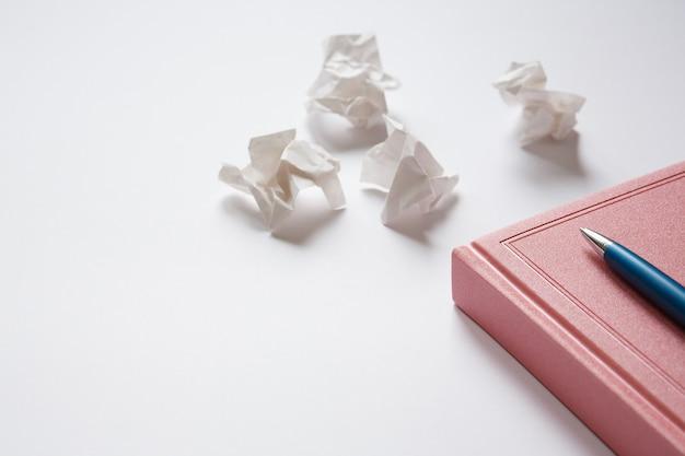 Pamiętnik i metalowy długopis na białym stole zmięte kawałki papieru. błędy w liście