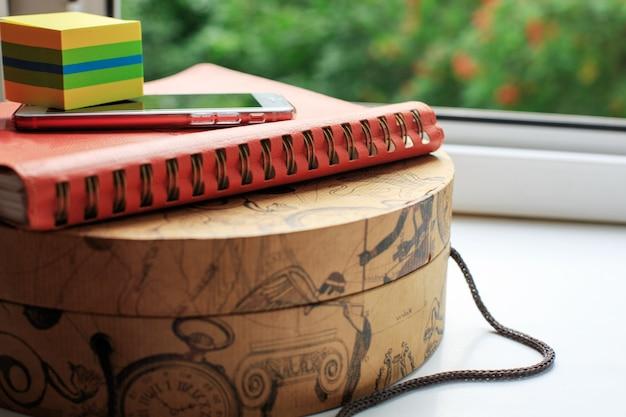 Pamiętnik i telefon komórkowy na okrągłym kartonie. pomysł na biznes