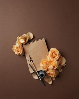Pamiętnik lub notatnik z długopisem i atramentem na notatki. notatnik z brązowymi stronami z pomarańczowymi różami