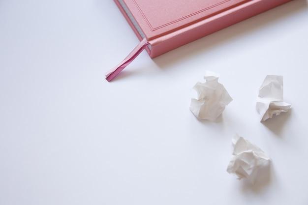 Pamiętnik na białym tle i zmięte kawałki papieru. błędy w liście