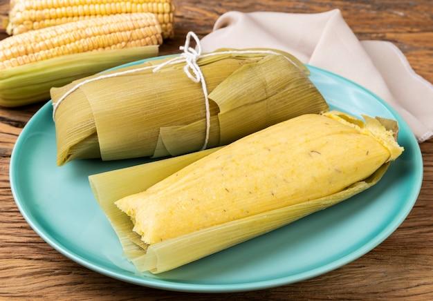 Pamonha, typowe brazylijskie jedzenie kukurydziane w niebieskim talerzu na drewnianym tle