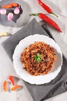 Pampis tongkol (tongkol suwir pedas), tradycyjne danie z owoców morza manado z pikantnych rozdrobnionych ryb, podawane na białej ceramicznej misce