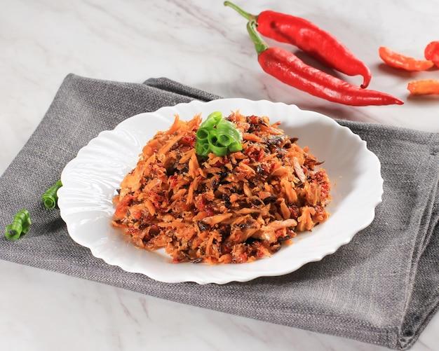 Pampis tongkol, tradycyjne danie z owoców morza manado z pikantnych rozdrobnionych ryb, podawane na białym talerzu ceramicznym. zwykle nazywany tongkol suwir pedas