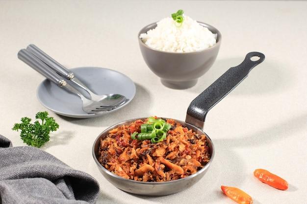 Pampis tongkol, tradycyjne danie z owoców morza manado z pikantnych rozdrobnionych ryb, podawane na żelaznej patelni z ryżem w ceramicznej misce