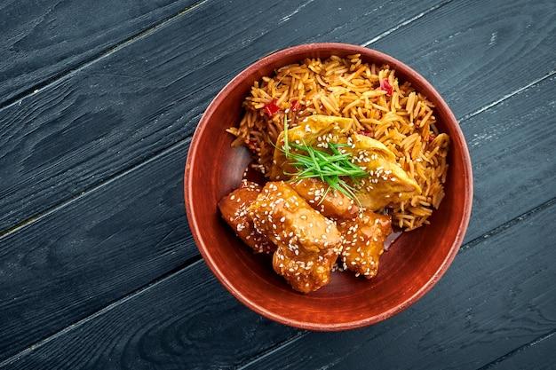 Pan-asian street food - słodko-kwaśny kurczak przyozdobiony ryżem, podawany w misce na drewnianej powierzchni. ryż z woka z kurczakiem. azjatyckie jedzenie. selektywne skupienie