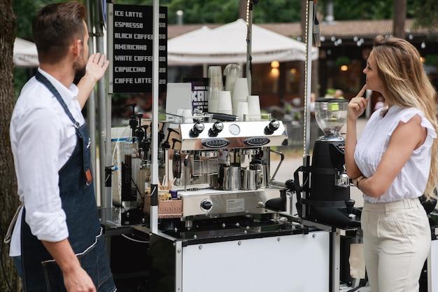 Pan barista proponuje klientce wybór różnych rodzajów kawy w swojej ruchomej kawiarni