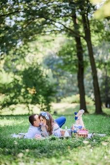 Pan młody przytula pannę młodą przetargu leżąc z nią na kocu podczas pikniku w zielonym parku