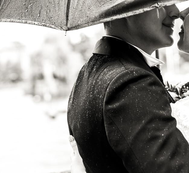 Pan młody całuje delikatną pannę młodą pod parasolem w deszczu