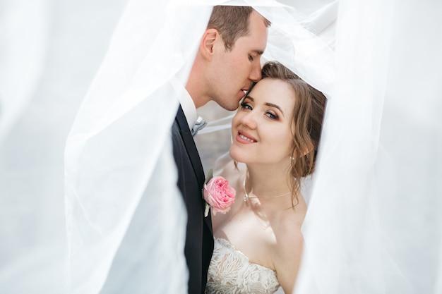 Pan młody całuje swoją ukochaną żonę