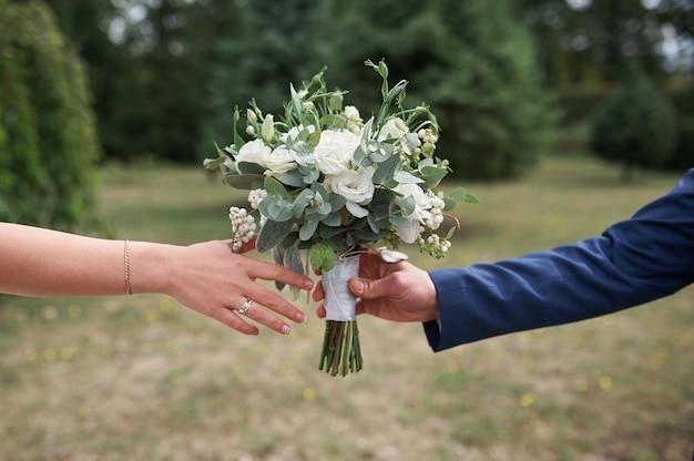 Pan młody daje pannie młodej piękny bukiet ślubny na spacerze