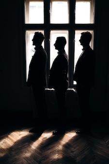 Pan młody i jego dwaj przyjaciele stoją w pobliżu okna hotelu