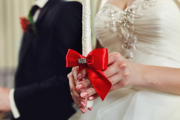 Pan młody i oblubienica ze świecami. ceremonia ślubna w kościele