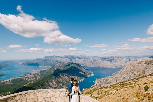 Pan młody i panna młoda obejmują się i patrzą na zatokę kotorską piękny widok z gór