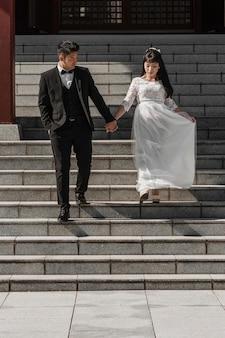 Pan młody i panna młoda schodzą po schodach