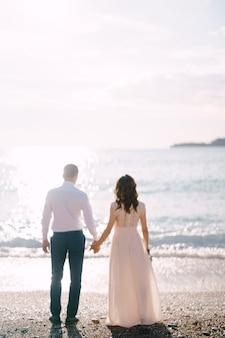 Pan młody i panna młoda stoją na plaży i patrzą na morze z tyłu