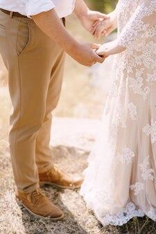 Pan młody i panna młoda stoją trzymając się za ręce na zbliżenie trawy