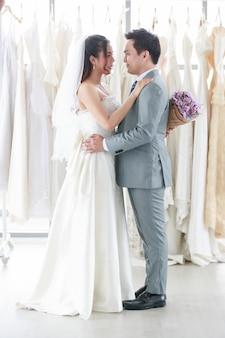 Pan młody i panna młoda stoją, uśmiechają się i przytulają w tle sukni panny młodej. kobieta trzyma fioletowy bukiet reprezentuje miłość do człowieka. koncepcja ślubu najlepszy dzień.