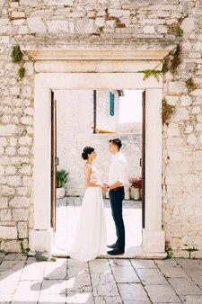 Pan młody i panna młoda w białej koronkowej sukience stoją przy wejściu do starego budynku trzymając się za ręce