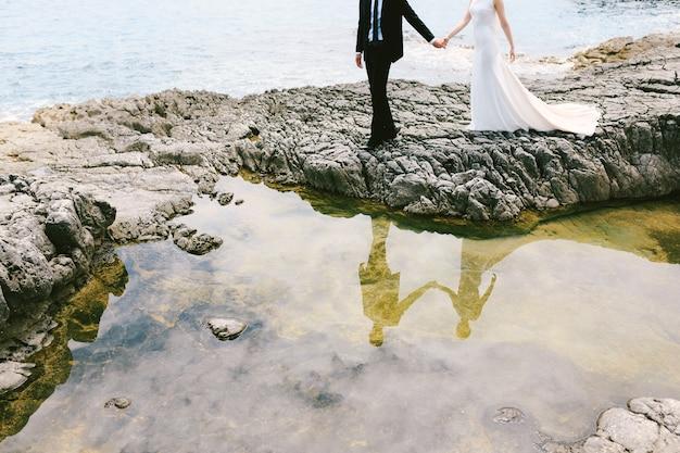 Pan młody i panna młoda w białej sukni trzymając się za ręce stoją na brzegu małego jeziora na skalistym brzegu